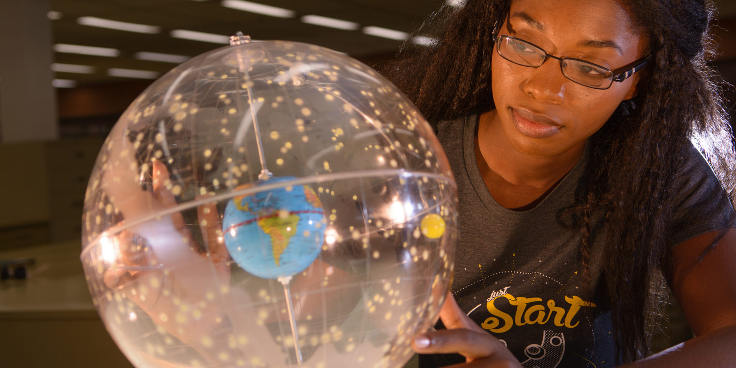 ASU student sitting with an innovation globe