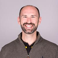 Stuart Rice, EdPlus employee, smiles wearing a grey collared sweater.